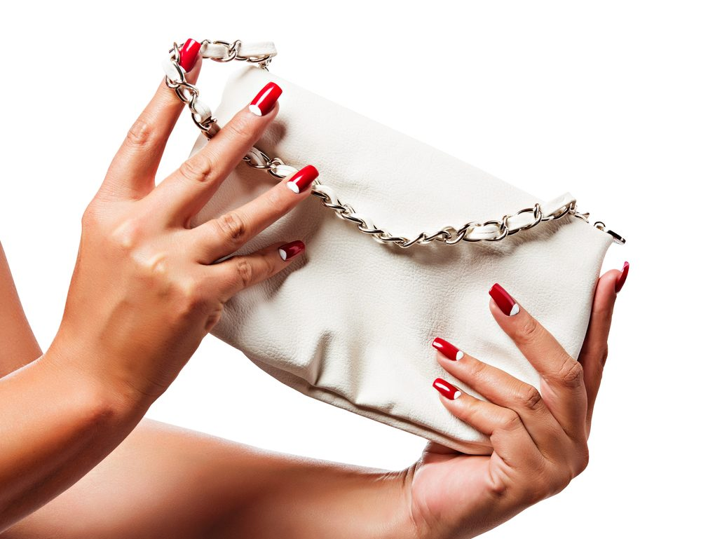 Red nails holding wallet